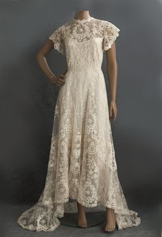 Princess lace wedding dress, c.1905: Antique princess lace and a gracefully trained back, from ivory cotton tulle hand-appliquéd with tape lace and closes in back with hooks and snaps.