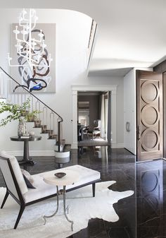 Designed by Neal Beckstedt Studio, the foyer of this home in New York's Westchester County features a black St. Laurent stone staircase and cast bronze balustrade.