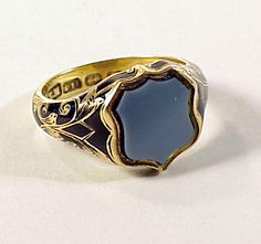 "Extremely fine Victorian memorial ring in 18K yellow gold, the shoulders with glossy black taille d'epargne enamel and engraved foliate decoration. A shield-shaped black and white sardonyx cartouche crowns the ring and covers a hair compartment visible through the beveled rock crystal cover on the inside of the ring. The inside of the shank is engraved ""Thomas Bland 1857 Obt 23 March 68 years"" and the compartment holds a woven plaque of his gray hair."