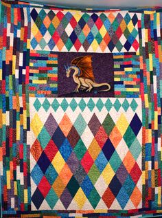 Dragon quilt with lots of jewel tone fabrics.