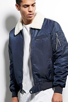 """A padded woven bomber jacket by Members Only™ featuring a sherpa basic collar, a zippered front with a snap-button flap hem, slanted front pockets with faux leather trim, an interior chest patch pocket, ribbed knit trim, the signature """"Members Only"""" tagged rib-knit chest pocket, bright contrast lining, and one zip-ring utility pocket with logo tag."""