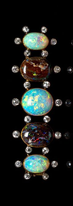 A Silver Topped Gold, Opal and Diamond Brooch, containing three oval cabochon cut crystal opals, the largest measuring approximately 12.22 x 10.50 mm and the other two measuring approximately 10.00 x 6.50 mm, two oval cabochon cut boulder opals measuring approximately 12.30 x 9.10 mm and 22 old European cut diamonds weighing approximately 1.21 carats total. 8.40 dwts.