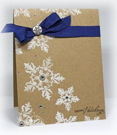Simple Christmas card idea. white snowflakes on brown with blue ribbon.
