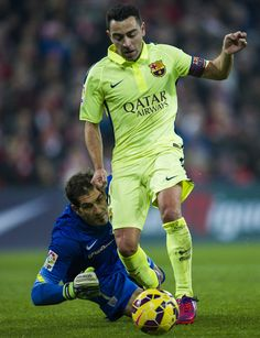 Xavi Hernandez of FC Barcelona duels for the ball with Gorka Iraizoz of Athletic Club during the La Liga match between Athletic Club and FC Barcelona at San Mames Stadium on February 2015 in Bilbao, Spain. Xavi Hernandez, Doha, Athletic Clubs, Sports Logo, Bilbao, Psg, Soccer Players, Fc Barcelona, Manchester United