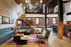 Midcentury living room in loft with brick walls and open staircase