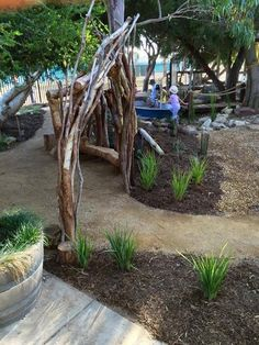 Pin 3. This Pin shows a created 'natural' environment playground that children are able to explore, interact and play with the built constructions and natural landscape setting. The built playground features characteristics such as trees, large playing area, vegetation, large stepping stones, wooden bridges, natural seating, walking arches, climbing trees as well as a range of other aspects.