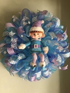 "Christmas Elf Wreath. This wreath is made on a very pretty variegated lavender and turquoise mesh. It features an adorable lavender and turquoise elf surrounded by lots and lots of very pretty white, lavender and turquoise wired ribbons and lots and lots of white glittered snowflakes. What a great way to welcome your family and friends this holiday season or hang this wreath on an interior wall of your home as part of your holiday decor. This wreath measures approximately 23"" in diameter."
