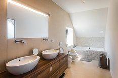 Koupelnu rodičů navrhli v přírodních tónech, které podporují příjemnou relaxaci a efekt zenové místnosti