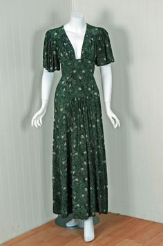 Green vintage dress by English fashion designer, Raymond Ossie Clark. This silk-rayon print dress is a flattering low-cut plunge hourglass with dramatic flutter-sleeves. Photo: Timeless Vixen