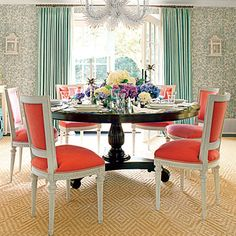 Bold Take on Tradition | The dining room of the historic Ernest Hemmingway home in Key West, Florida proves that formal doesn't have to be fussy. In this case, the dark wood of the traditional pedestal table is set off by bright tropical colors. Coral-upholstered chairs surround the table, turquoise draperies frame the window, and a showstopping chandelier adds sparkle.