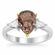 The classic look of this 18K two-tone gold ring featuring a 2.53 carat pear-shaped Fancy Dark Orange-Brown diamond makes a surprisingly dainty statement. The stunning cognac-hued center diamond is flanked by a pair of tapered baguettes. The dark center stone is a beautiful contrast against the white side stones.