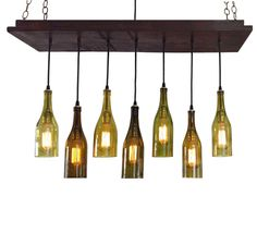 7 Recycled Wine Bottle Chandelier Rustic style chandelier handmade from hard wood and stained a rich walnut brown color. Wiring is black with antique gilt hardware. Seven cascading recycled wine bottle pendants. Details: Canopy: 9.25 x 38 7 Wine Bottle Pendants (olive, amber)