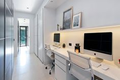 In this hallway, there's a small study area that's been built-in. Hidden lighting underneath a picture rail provides a soft, ambient light for the work area.