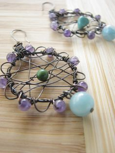 Dream Catcher Earrings - Created from oxidized brass with lovely contrasts of greens and purple. Wrapped in beautiful Amethyst while turquoise beads are nestled in the center. Amazonite rounds dangle at the bottom of each hoop.