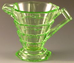 Tea Room Green Depression Glass Creamer, 1926-31, Indiana. Back in the 1920s every drug store had a soda fountain and department stores had tea rooms where you could get a small lunch or light snack.  Ice cream sodas and floats were menu favorites.  Indiana marketed Tea Room to these small restaurants and offered many tumblers and dishes that fit the ice cream and snack menus.  For example Indiana made four different creamers and sugars to choose among.