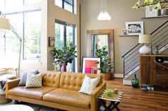 Warm wood tones, earthy colors, eclectic art and accessories, modern caramel leather sofa --Erin's Modern Loft House Tour | Apartment Therapy