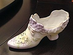 THIS IS A BEAUTIFUL ANDREA BY SADEK PORCELAIN DECORATIVE SHOE FIGURINE IT FEATURES PALE VIOLET AROUND TOP AND FOOT WITH BEAUTIFUL YELLOW AND PURPLE FLOWERS. GOLD TRIM AROUND TOP AND HEEL OF SHOE.LABEL ON BOTTOM WITH # 11725SHOE MEAUSRES: 3 1/4 HIGH BY 6 3/8 INCHES LONGEXCELLENT CONDITION