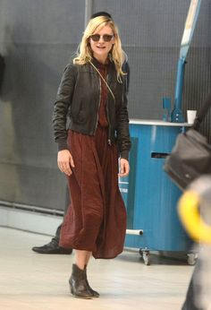 Kirsten Dunst travel outfit- midlength flowy dress with ankle boots and leather jacket