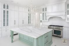 A+whitewashed+French+candle+chandelier+illuminates+a+mint+green+kitchen+island+with+turned+legs+topped+with+white+marble+with+gray+veining+fitted+with+a+farmhouse+sink+and+deck+mount+faucet.