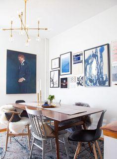 Mesa de comedor color caoba de estilo sónico o vintage con un par de sillas Eames negras, otro par de sillas Lilla Aland de madera color celeste pálido y un par de sillas Wishbone en madera color natural.