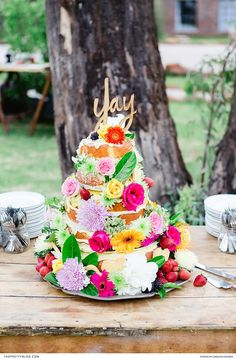 Covered in striking flowers from top to bottom, this cake was a vision to behold and served as a spectacular focal point for a fun-filled wedding reception. | Photographer: Carolien and Ben | Confectioner: Hes Potgieter