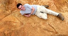 Dr. Knoll lies next to the exceptionally large carnivorous dinosaur footprints found in Lesotho. Image credit: Fabien Knoll.