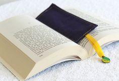 Marque-page en tissu violet avec ruban jaune et breloque en métal et résine. Résistant au lavage 30°. Taille (HXL) : 16 x 6 cm Ce marque-page est parfait pour ne plus perdre la fameuse page... Finis les marques-page en papier qui s'abîment et se déchirent. Plus de risque avec son petit ruban qui vous permettra de rouvrir votre livre pile poil ou vous l'aviez arrêté! Alors croquez vos livres à pleine dents :)