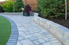 Roman Sierra Grey Stackstone Retaining Wall and Roman Paver with Charcoal Holland Border