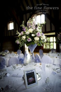ivory & lilac wedding flowers - roses, hydrangeas, delphiniums and lisianthus Martini vases from Great Fosters wedding