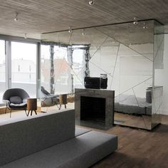Wrinkly mirrored walls distort the reflection of an apartment interior in Berlin by local architects Lecarolimited.