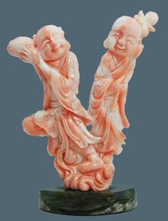 Chinese hand carved pink coral group figure depicting elders. Highly detailed figure depicting two elders . The woman is holding a flower and the man is holding a clam shell. Set on green marble round base.