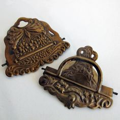 """Pair Victorian Clips from Curious Sofa.  Use these brass clips to hang any print instantly. Embossed metal with an antique design. Hinged clip can hold any item up to 1/4"""" thick. Great for photos, prints or leave on a desk to organize papers. Set of 2 styles. Hole on the back for hanging.  3.25"""" wide $14.95"""