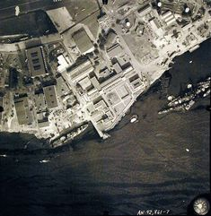"80-G-387568: Pearl Harbor Attack, 7 December 1941. Aerial view of ""Battleship Row"" moorings on the southern side of Ford Island, 10 December 1941, showing damage from the Japanese raid three days earlier. USS California (BB 44) and USS Curtiss (AV 4) are shown. Note dark oil streaks on the harbor surface, originating from the sunken battleships. Photographed by VJ-1 at an altitude of 3,000 feet and released November 9, 1950."