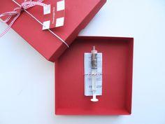 Ein origenelles Geldgeschenk, über das sich bestimmt jeder freut. In einer hübschen Schachtel aus rotem Karton befindet sich eine Spritze die gar nicht weh tut, sondern maximal Freudentränen...
