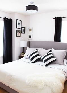 King size gray headboard with nail trim. Bedroom gallery wall. off center window. Sexy black curtains. Black and white bedroom decor. Small spaces. Big Style. Chic master bedroom.   INTERIOR DESIGN - BLACK & WHITE BEDROOM — Splendor in Spanglish