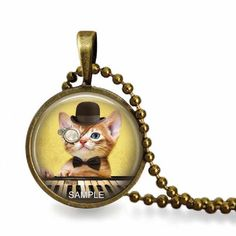 """Glass tile steampunk necklace with a glass tile pendant that has an image of a piano playing steampunk monocle wearing orange tabby kitten.  The laser printed image has been adhered and sealed to a round 1"""" bronze pendant tray and domed glass tile. The ..."""