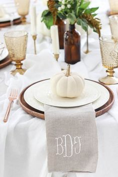 Thanksgiving Tablescape | 2018 | Beautiful fall tables cape with greenery, amber bottles, mini white pumpkins, monogram napkins, vintage tinted glasses, gold rimmed cocktail glasses, and candlesticks. #tablescape #falldecor