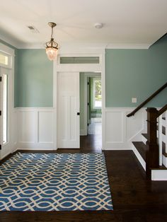 dark plank flooring, white paneling/chair rail, white stair risers, dark steps, pocket door, white/blue rug, pendant light