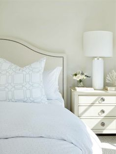 White and ivory bedroom features an ivory nailhead camelback headboard on king bed dressed in white and gray bedding placed next to an ivory nightstand adorned with nickel ring pulls and a white glass column lamp. Ivory Bedroom, Master Bedroom Interior, Calm Bedroom, Grey And White Bedding, Elegant Bedroom Design, Small Bedroom Storage, How To Dress A Bed, Comfortable Pillows, Traditional Bedroom Decor