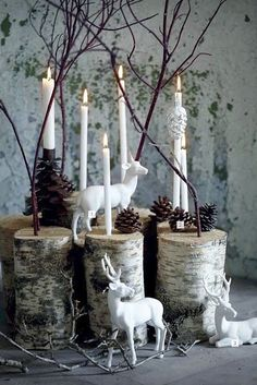 Candle holders created by drilling lengths of birch log, inserting plain white candles, branches - surround with ornaments such as white ceramic deer (mercury glass ornaments would also be a perfect accent)
