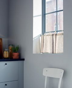 In a kitchen, a kitchen towel hangs from a curtain wire in the window.
