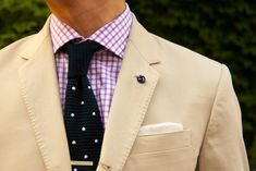 Knit tie, tie clip and silk knot on lapel.