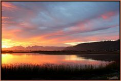 Sunset in Sedgefield over Swartvlei lagoon with Outeniqua mountains in the back.