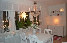 adventsstjärna,adventsstake,ljus,takkrona,köksbord,stolar,köpmandisk,rött,vitt,blommor,hyllor,kök,jul