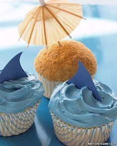 """Beach/Nautical Party: paper whale/shark fins in blue icing and cocktail umbrella in graham cracker (?) """"sand"""" cupcakes"""