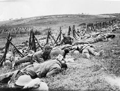 BATTLE SOMME 1 JULY - 18 NOVEMBER 1916 (CO 205) Men of the Royal Warwickshire Regiment, their rifles stacked nearby, lying exhausted in the grass in a rear area.