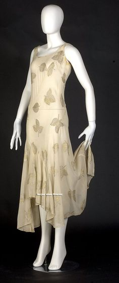 Evening dress, French, circa 1930. Gold and silver metallic leaves float down on cream silk chiffon. Likely it was worn over a pale form-fitting silk slip. Dress spirals in 3 pieces around the body with diagonal seams from left shoulder to right hip. This bias stretch eliminates need for any openings. Eight godets in skirt, nearly doubling fullness at the calves. Edges of hem, neckline, armscyes, and inside seams bound with hand-rolled and stitched chiffon. Via Smith College Historic Clothing.