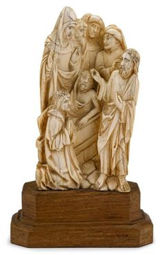South German ivory figure group, the Raising of Lazarus   17th century   Carved to show Christ with his hand touching the head of Lazarus as he emerges from the tomb, as astonished witnesses look on, raised on wooden plinth