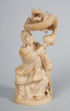 Japanese carved ivory sage with dragon modeled as robed mystic with dragon emerging from pot, 6 in. H.