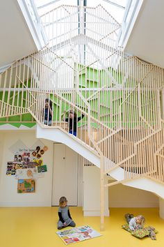 The design revolves around a wooden tree-like structure that connects the open-plan ground floor with an elevated platform for quiet play, reading and sleeping.